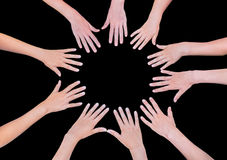 Cinco manos de los niños que se unen a en círculo sobre fondo negro Foto de archivo libre de regalías