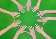 Cinco manos de los niños que se unen a en círculo sobre fondo verde Fotografía de archivo