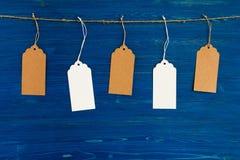 Cinco marrons e grupo branco dos preços ou de etiquetas do papel vazio que pendura em uma corda no fundo azul Fotografia de Stock Royalty Free