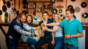 Cinco mejores amigos tintinean los vidrios en la barra y la risa Foto de archivo libre de regalías