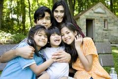 Cinco miúdos que sentam-se no banco Imagens de Stock Royalty Free