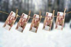 Cinco mil cédulas do rublo de russo que penduram em uma corda com os Pegs de roupa no fundo borrado da floresta do inverno Imagens de Stock Royalty Free