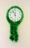 Cinco minutos a doce en el reloj de pared viejo adornado con malla verde Fotos de archivo libres de regalías