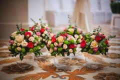 Cinco mismos ramos de rosas multicoloras en floreros Fotografía de archivo
