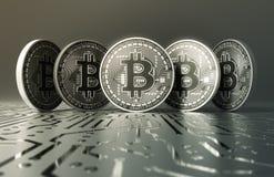 Cinco moedas de prata virtuais Bitcoins na placa de circuito impresso Fotos de Stock Royalty Free
