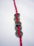 Cinco monedas antiguas chinas encadenadas con una cuerda roja Imágenes de archivo libres de regalías