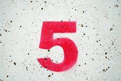 Cinco números vermelhos em fundos concretos e brancos velhos Imagens de Stock