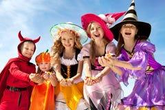 Cinco niños de Halloween que sostienen los caramelos Foto de archivo libre de regalías