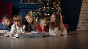 Cinco niños elegantes que escriben algo en el papel mientras que se relaja en el cuarto almacen de video