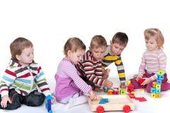 Cinco niños que juegan los juguetes Imagenes de archivo