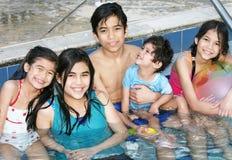 Cinco niños que se sientan en piscina Imagen de archivo libre de regalías