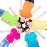 Cinco niños sonrientes que mienten en el piso. Foto de archivo libre de regalías