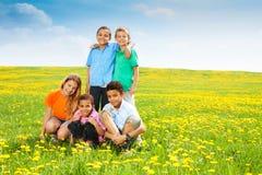 Cinco niños felices en dientes de león Imagen de archivo libre de regalías
