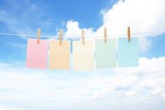 Cinco notas en colores pastel coloridas sobre clavijas Imagenes de archivo