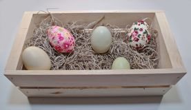 Cinco ovos da páscoa coloridos diferentes em uma caixa de madeira imagens de stock