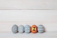 Cinco ovos da páscoa feitos a mão coloridos em um fundo de madeira, um fizeram sob a forma de um manequim para testes do impacto foto de stock royalty free
