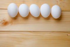 Cinco ovos em uma tabela de madeira Foto de Stock