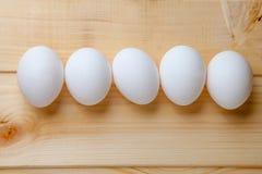 Cinco ovos em uma tabela de madeira Fotos de Stock