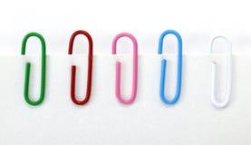 Cinco Paperclips de los colores en el fondo blanco Foto de archivo libre de regalías