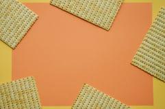 Cinco pedazos de Matzo en el fondo coralino y amarillo Espacio vac?o para el texto Concepto de moda foto de archivo libre de regalías