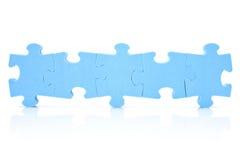 Cinco pedazos del rompecabezas conectados en una fila Imágenes de archivo libres de regalías