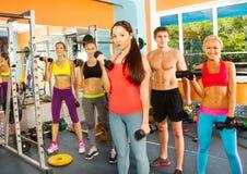 Cinco personas jovenes agradables en el club de fitness imagen de archivo libre de regalías