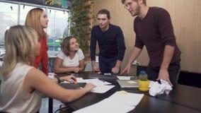 Cinco personas jovenes que discuten intenso planes en la tabla de la sala de reunión Planes empresariales diarios del análisis almacen de metraje de vídeo