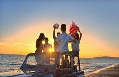 Cinco personas jovenes que se divierten en coche convertible en la playa en la puesta del sol Imagenes de archivo