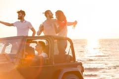 Cinco personas jovenes que se divierten en coche convertible en la playa en la puesta del sol Foto de archivo libre de regalías