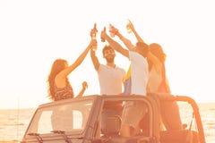 Cinco personas jovenes que se divierten en coche convertible en la playa en la puesta del sol Foto de archivo