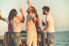 Cinco personas jovenes que se divierten en coche convertible en la playa en la puesta del sol Fotografía de archivo