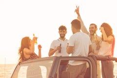 Cinco personas jovenes que se divierten en coche convertible en la playa en la puesta del sol Fotos de archivo libres de regalías