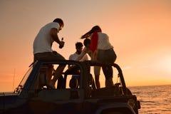 Cinco personas jovenes que se divierten en coche convertible en la playa en la puesta del sol Fotografía de archivo libre de regalías