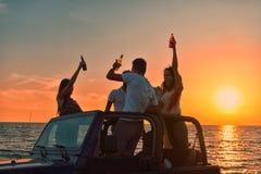 Cinco personas jovenes que se divierten en coche convertible en la playa en la puesta del sol Imágenes de archivo libres de regalías