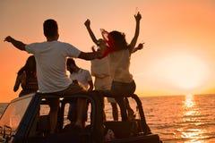 Cinco personas jovenes que se divierten en coche convertible en la playa en la puesta del sol Fotos de archivo