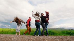 Cinco personas jovenes saltan y sonríen en el campo verde almacen de metraje de vídeo