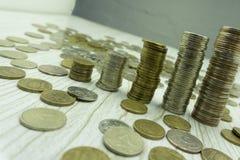 Cinco pilhas de moedas com crescimento entre o empilhamento de limites no fundo branco fotos de stock royalty free