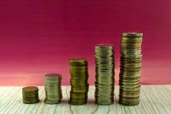 Cinco pilhas de moedas com crescimento entre o empilhamento de limites no fundo branco fotos de stock