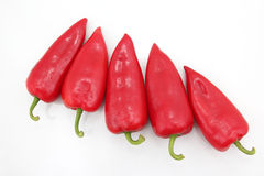 Cinco pimientas dulces rojas brillantes en un fondo blanco Fotos de archivo libres de regalías