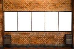 Cinco quadros de avisos vazios na parede de tijolo Imagens de Stock Royalty Free