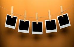 Cinco quadros vazios do Polaroid que penduram na guita Fotos de Stock Royalty Free