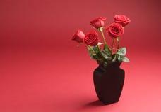 Cinco rosas no vaso no fundo vermelho imagens de stock