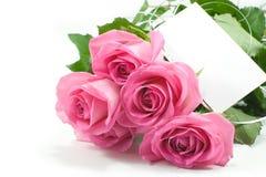 Cinco rosas rosadas con la tarjeta en blanco Fotografía de archivo