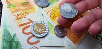 Cinco shekels israelíes acuñan en los fingeres de las personas sobre la pila de nuevos billetes de banco imagen de archivo