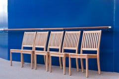 Cinco sillas de madera por el tabique hermético azul Imagenes de archivo