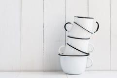 Cinco tazas esmaltadas blanco Foto de archivo