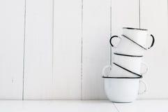 Cinco tazas esmaltadas blanco Imagenes de archivo