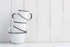 Cinco tazas esmaltadas blanco Fotos de archivo libres de regalías