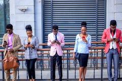 Cinco trabalhadores de escritório que estão com telefones de móbeis e sms de datilografia entre si fotografia de stock