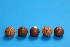 Cinco trufas de chocolate en una fila Fotografía de archivo libre de regalías